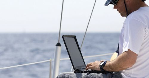 Businessman with laptop computer on sailboat.