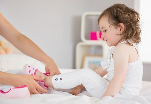 Side view of mother dressing up young daughter on bed at home